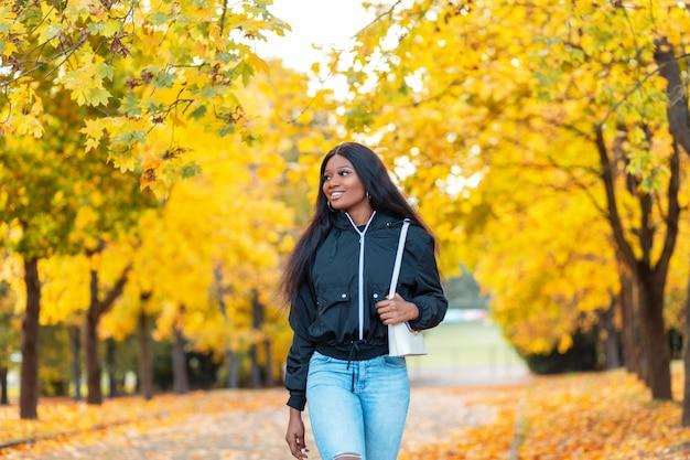 Szczęśliwa piękna afroamerykanka ze słodkim uśmiechem w modnej casualowej kurtce z niebieskimi dżinsami i torebką spaceruje po naturze w pobliżu drzew z jasnożółtymi jesiennymi liśćmi