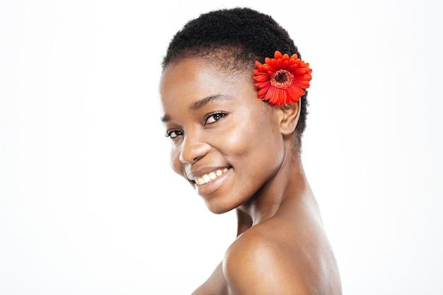 Szczęśliwa piękna afroamerykańska kobieta z kwiatem patrząca na kamerę na białym tle