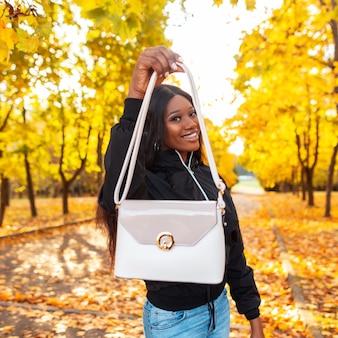 Szczęśliwa piękna afrykańska czarna kobieta z uśmiechem w modne ubrania i kurtkę pokazując białą skórzaną torebkę w parku z jasnożółtymi jesiennymi liśćmi. kobiecy styl casual z modną torbą