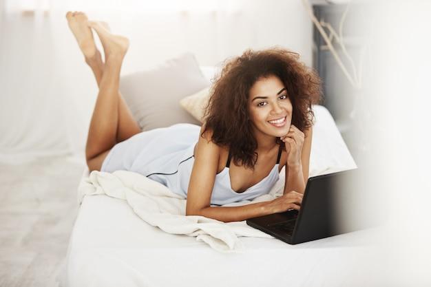 Szczęśliwa piękna afrykańska kobieta w sleepwear lying on the beach z laptopem na łóżka ono uśmiecha się w domu.