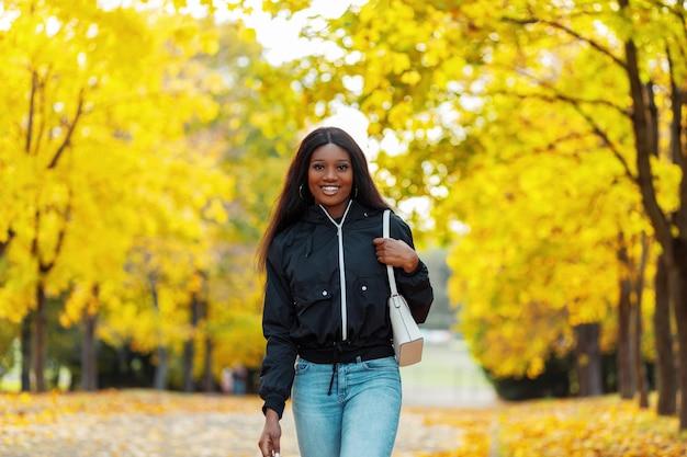 Szczęśliwa piękna afrykańska uśmiechnięta kobieta z czarną skórą w modnych ubraniach z kurtką, dżinsami i torebką spaceruje po jesiennym parku z żółtymi jesiennymi liśćmi