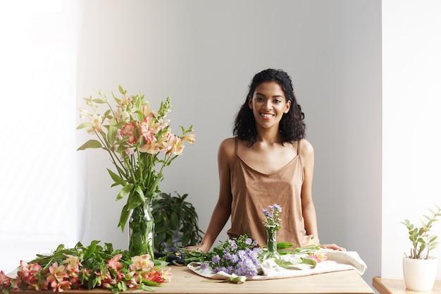 Szczęśliwa piękna afrykańska żeńska kwiaciarnia ono uśmiecha się przy miejscem pracy w kwiatu sklepie. skopiuj miejsce