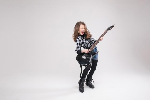 Szczęśliwa piękna artystyczna mała dziewczynka bawić się gitarę