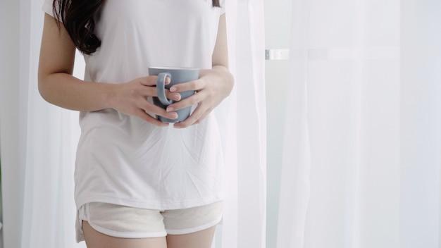 Szczęśliwa piękna azjatycka kobieta ono uśmiecha się i pije filiżankę kawy lub herbaty blisko okno w sypialni.