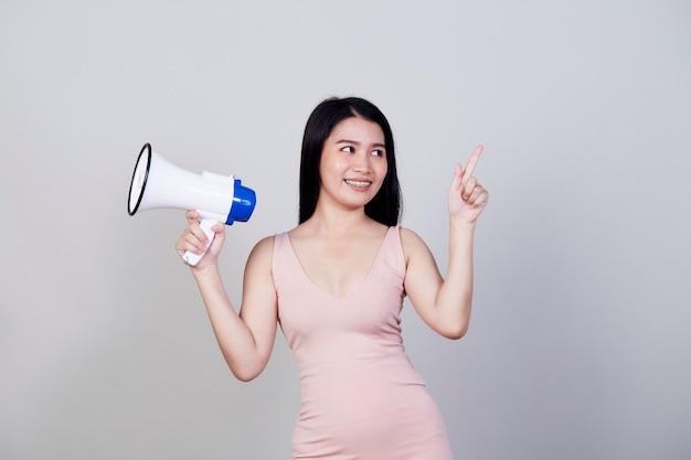 Szczęśliwa piękna azjatycka kobieta rozmawia przez magafon na białym tle na jasnoszarym tle z miejsca na kopię