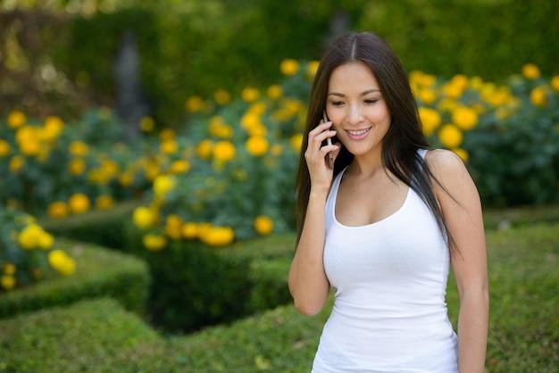 Szczęśliwa piękna azjatycka kobieta rozmawia przez telefon w parku na świeżym powietrzu
