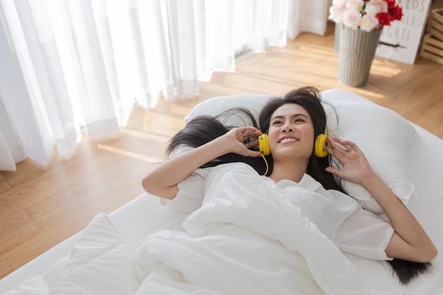 Szczęśliwa piękna azjatycka młoda kobieta relaksuje i słucha z headphonmusic es podczas gdy kłamający na białym łóżku w przypadkowej odzieży.