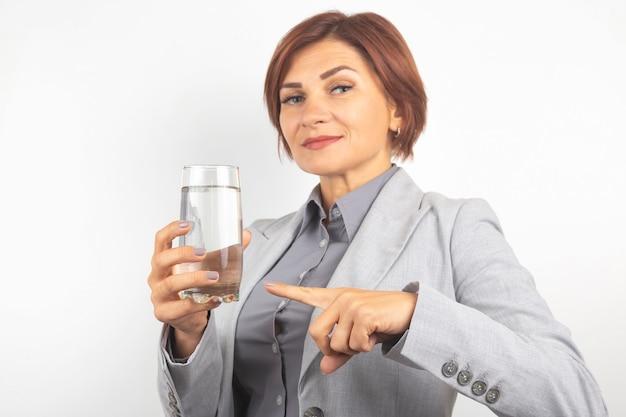 Szczęśliwa piękna biznesowa kobieta oferuje szklankę wody. pragnienie i zdrowie.