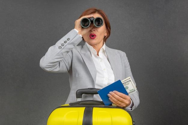 Szczęśliwa piękna biznesowa kobieta patrzy przez lornetkę z zaskoczenia w kierunku jej podróży.
