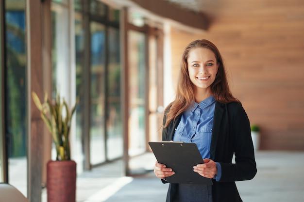 Szczęśliwa piękna biznesowa kobieta z schowkiem w biurze.