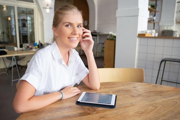 Szczęśliwa piękna blondynka z tabletem siedzi przy stole w przestrzeni coworkingowej