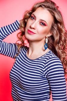 Szczęśliwa piękna brunetka dziewczyna z czerwonym makijażem, kręconymi włosami i swetrem w niebieskie paski, pozowanie na czerwonym tle. zdjęcie pionowe