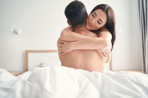 Szczęśliwa piękna ciemnowłosa młoda kaukaska kobieta z zamkniętymi oczami przytulająca mężczyznę w łóżku
