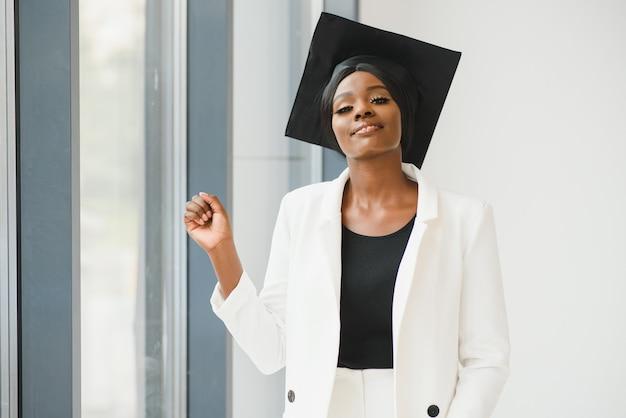 Szczęśliwa piękna czarna afroamerykańska dziewczyna z absolwentami kapeluszy