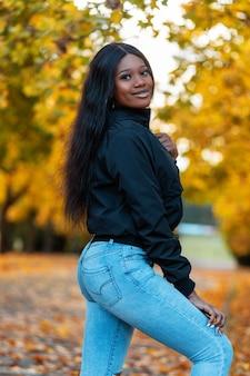 Szczęśliwa piękna czarna kobieta z casualową kurtką z modnymi niebieskimi dżinsami w parku z kolorowymi żółtymi jesiennymi liśćmi