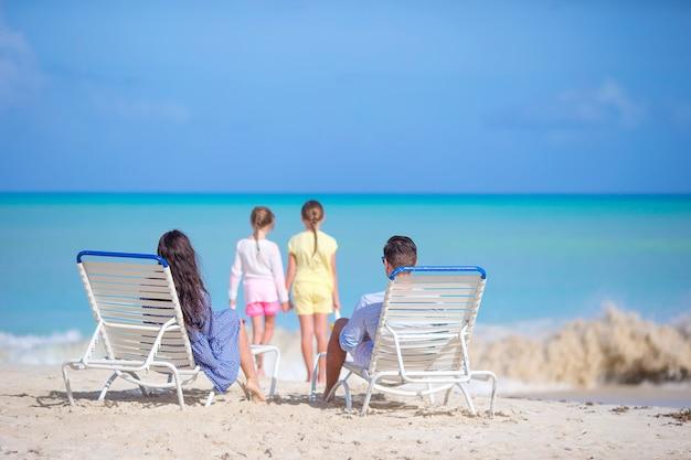 Szczęśliwa piękna czteroosobowa rodzina na plaży.