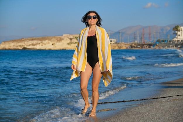 Szczęśliwa piękna dojrzała kobieta w stroju kąpielowym z ręcznikiem spacerowym wzdłuż morza