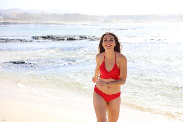 Szczęśliwa piękna dziewczyna bikini wychodzi z wody spaceru, ciesząc się tropikalną plażą