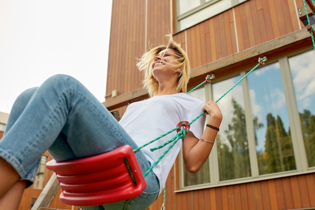 Szczęśliwa piękna dziewczyna na huśtawce. przeciwko jego domu. blondynka śmieje się i kołysze na huśtawce dla dzieci. rodzinne szczęście, rozrywka, relaks w domu.