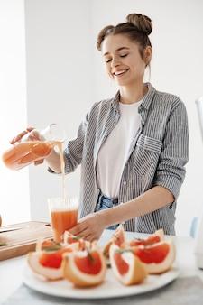Szczęśliwa piękna dziewczyna nalewa grapefruitowego detox smoothie w szkle ono uśmiecha się nad biel ścianą. zdrowe odżywianie.