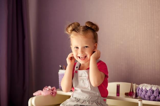 Szczęśliwa piękna dziewczyna siedzi na komodzie z makijażem śmiejąc się