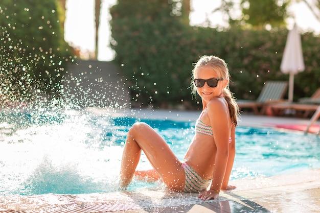 Szczęśliwa piękna dziewczyna w bikini i okularach przeciwsłonecznych bawi się na basenie