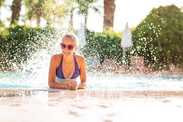 Szczęśliwa piękna dziewczyna w bikini i okularach przeciwsłonecznych pozuje na basenie