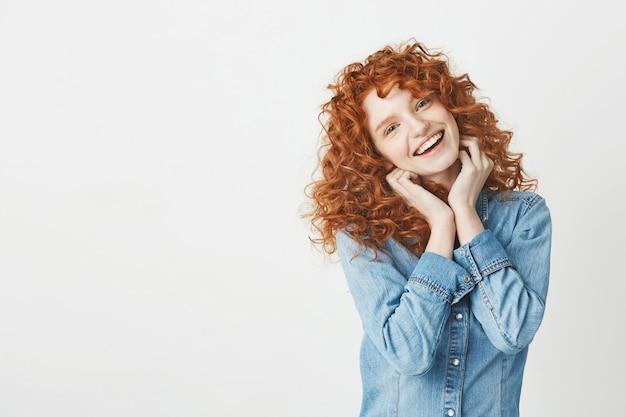 Szczęśliwa piękna dziewczyna z kędzierzawy czerwony włosiany ono uśmiecha się. skopiuj miejsce