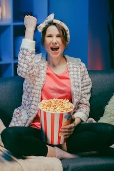 Szczęśliwa piękna dziewczyny twarz ogląda komediowego film w domu. tysiącletnia kobieta siedzi na kanapie i ogląda telewizję. pojęcie rozrywki. pozytywne emocje