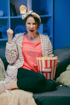 Szczęśliwa piękna dziewczyny twarz ogląda komediowego film w domu. tysiącletnia kobieta siedzi na kanapie i ogląda telewizję.