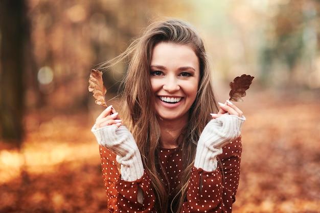Szczęśliwa piękna kobieta bawi się jesienią w lesie