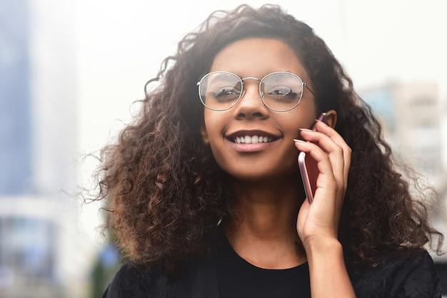 Szczęśliwa piękna kobieta chodząca i pisząca lub czytająca wiadomości sms