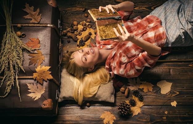 Szczęśliwa piękna kobieta czyta książkę na jesiennych żółtych liściach