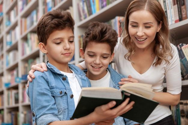 Szczęśliwa piękna kobieta i jej śliczni młodzi synowie czytają książkę w lokalnej bibliotece
