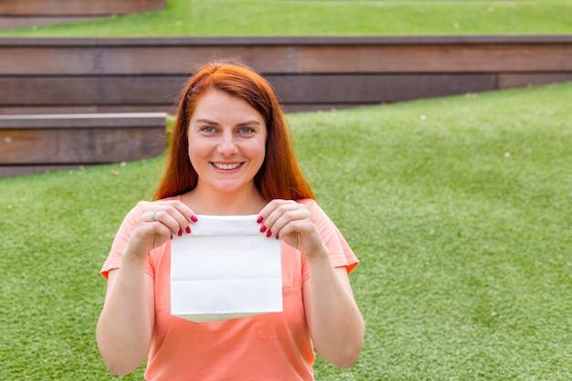 Szczęśliwa piękna kobieta imbir trzyma w dłoniach białą papierową torbę. kobieta trzyma pakiet z jedzeniem. skopiuj miejsce