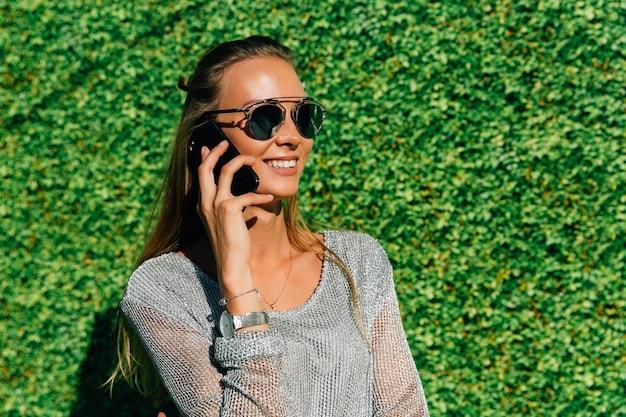 Szczęśliwa piękna kobieta ma rozmowę telefoniczną, radośnie ono uśmiecha się, będący ubranym okulary przeciwsłonecznych