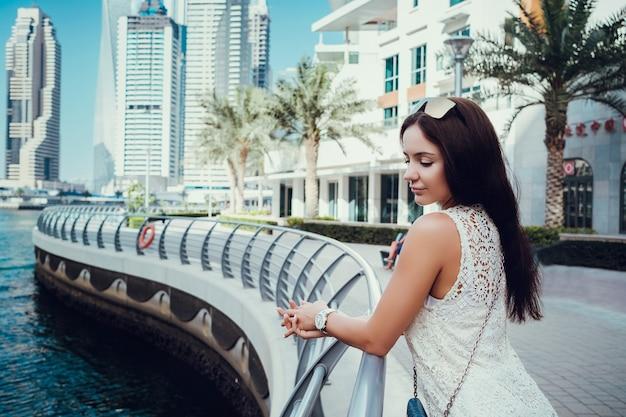 Szczęśliwa piękna kobieta nie do poznania turysta w modnej letniej białej sukni, ciesząc się w dubaju