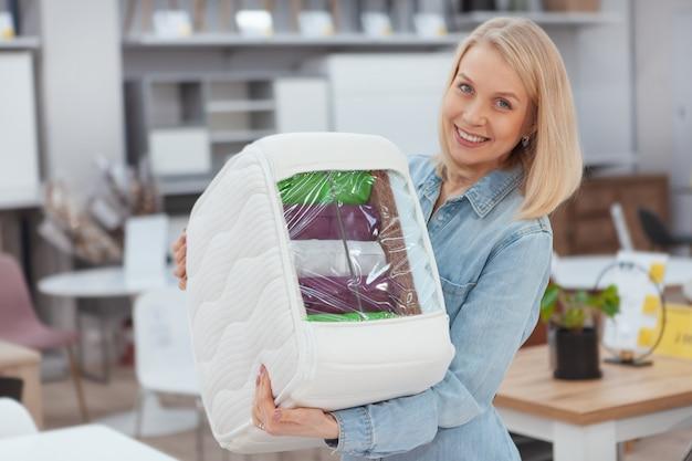 Szczęśliwa piękna kobieta ono uśmiecha się kamera trzyma ortopedyczną materac próbkę, robi zakupy przy meblowanie sklepem