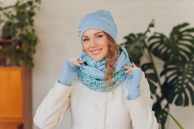 Szczęśliwa piękna kobieta, patrząc z ukosa w podnieceniu. dziewczyna ubrana w ciepły kapelusz z dzianiny i rękawiczki.