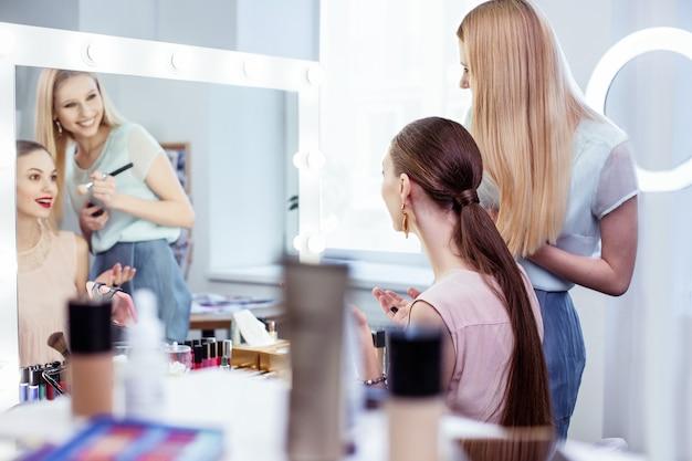 Szczęśliwa piękna kobieta patrząca w lustro, ciesząc się, jak wygląda