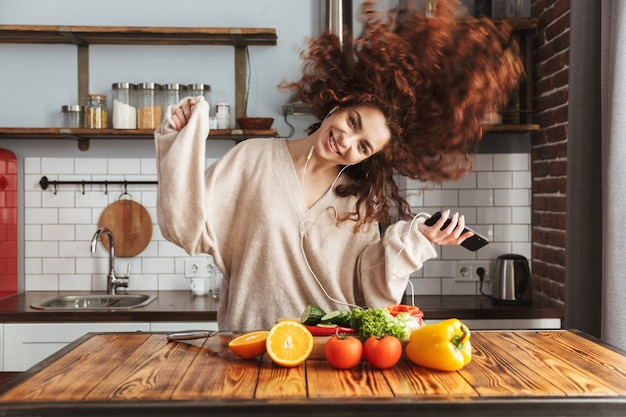 Szczęśliwa piękna kobieta słucha muzyki na telefonie komórkowym podczas gotowania sałatki ze świeżych warzyw w kuchni w domu