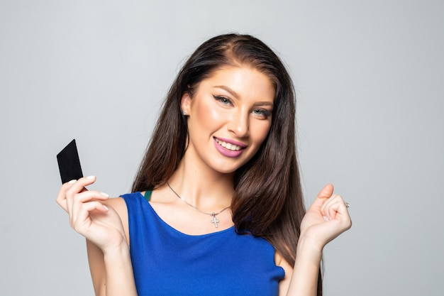 Szczęśliwa piękna kobieta trzyma kredytową kartę odizolowywająca nad biel ścianą.