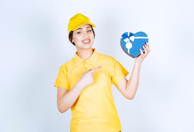 Szczęśliwa piękna kobieta trzymająca pudełko w kształcie serca i wskazująca na nim palcem