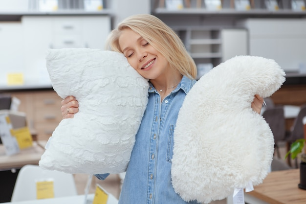 Szczęśliwa piękna kobieta uśmiecha się z zamkniętymi oczami, ściskając duże puszyste poduszki