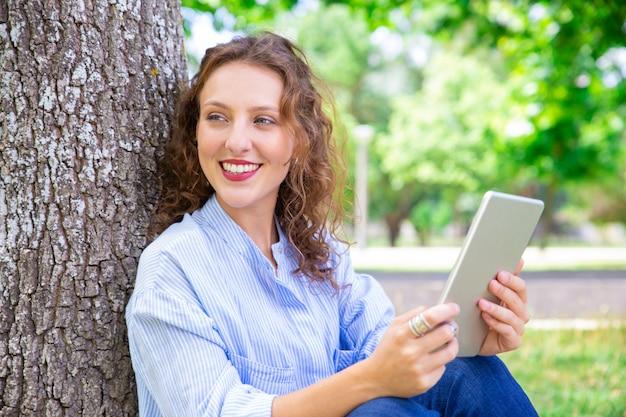 Szczęśliwa piękna kobieta używa mobilnego internet na pastylce