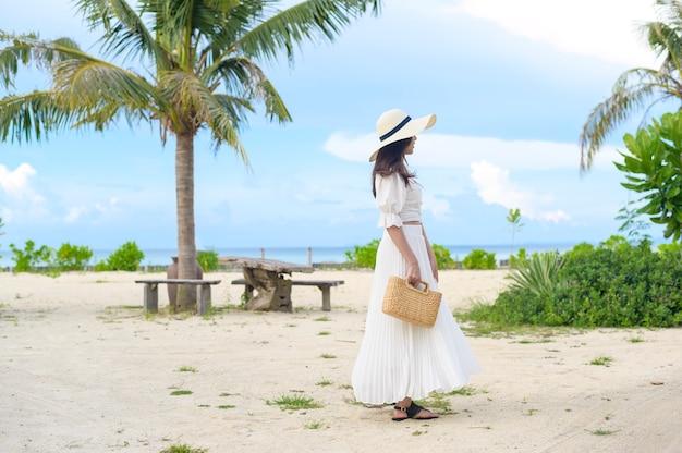 Szczęśliwa piękna kobieta w białej sukni, ciesząca się i relaksująca na plaży