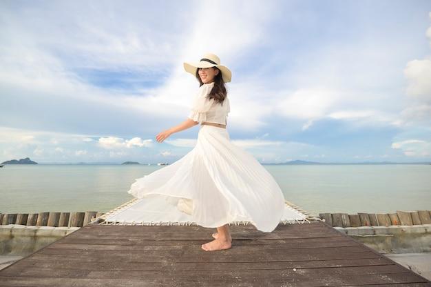 Szczęśliwa piękna kobieta w białej sukni, ciesząca się i relaksująca na tarasie na tropikalnej wyspie i turkusowym, czystym oceanie
