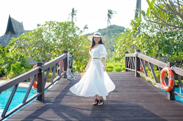 Szczęśliwa piękna kobieta w białej sukni, ciesząca się i stojąca na drewnianym moście nad basenem w przytulnym bungalowie