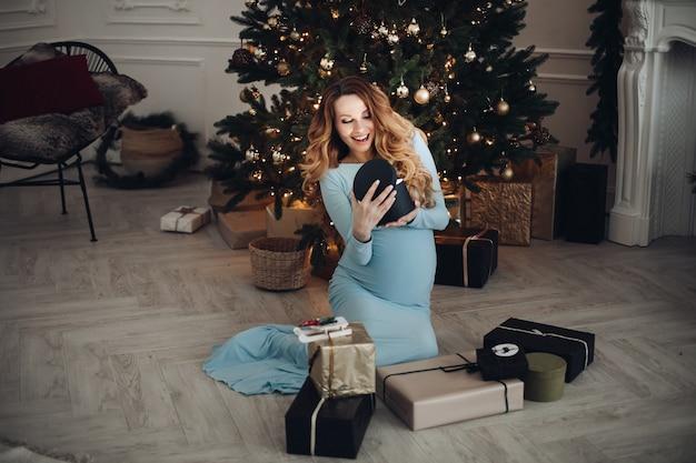 Szczęśliwa piękna kobieta w ciąży trzymająca pudełko z prezentem