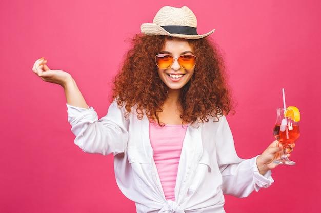 Szczęśliwa piękna kobieta w letnie ubranie ze szklanką drinka koktajlowego strzał studio na białym tle na kolorowe różowe tło
